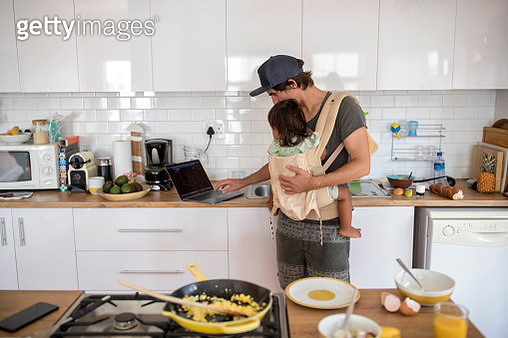 Father with a toddler in a baby carrier and a laptop in the kitchen - gettyimageskorea