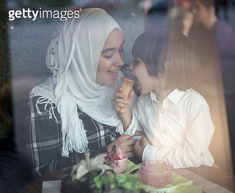 Young Muslim Mother at Restaurant with Her Son - gettyimageskorea
