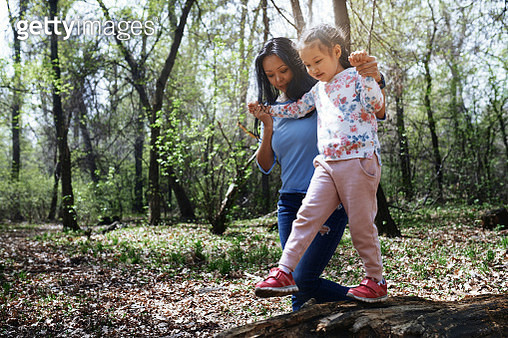 Mother and daughter in park, girl balancing on tree trunk - gettyimageskorea