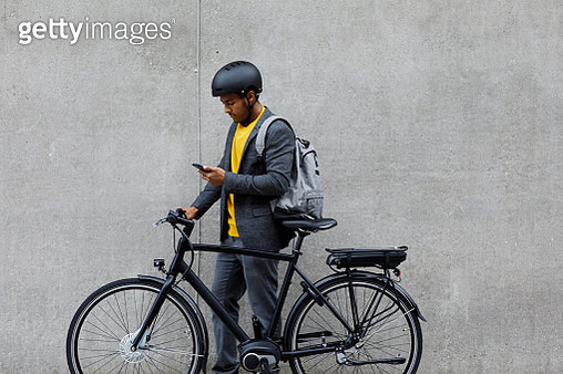 Young man standing by electric bicycle using smartphone - gettyimageskorea
