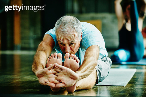 Man in seated forward bend pose during yoga class - gettyimageskorea