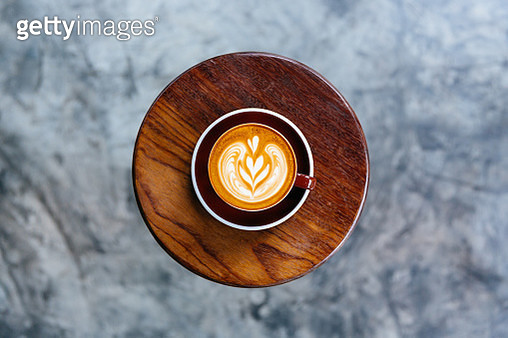 Cup of coffee standing on a round coffee table - gettyimageskorea