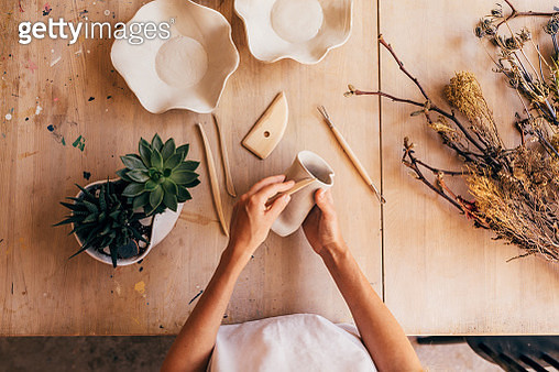 Midsection Of Woman Making Pottery On Table In Workshop - gettyimageskorea