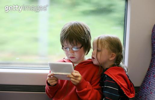 Siblings playing handheld console - gettyimageskorea