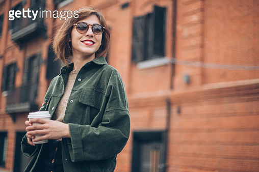 One young woman, relaxing in city alone, holding a cup o coffee. - gettyimageskorea