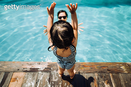Overhead view of little Asian toddler girl having fun and jumping into her mother's arms in the swimming pool in Summer - gettyimageskorea