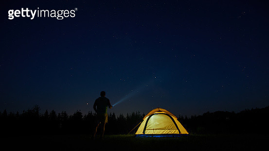 Rear View Of Man Flashing Light In Sky While Standing By Tent At Night - gettyimageskorea