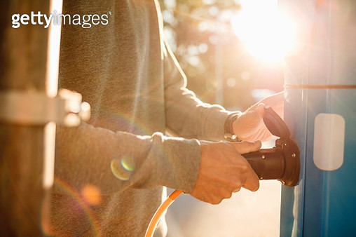 Midsection of man plugging at electric station on sunny day - gettyimageskorea
