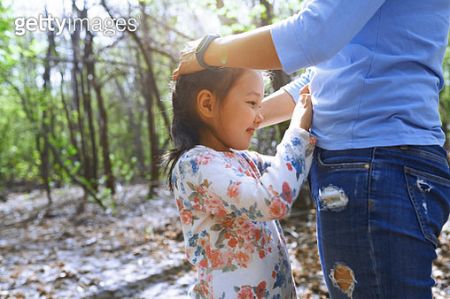 Daughter touching mother's belly in a park - gettyimageskorea