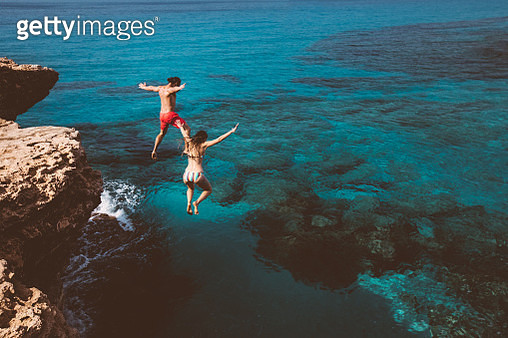Young active man and woman diving from high cliff into tropical island blue sea water - gettyimageskorea
