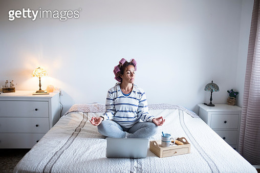 Woman with hair curlers meditating on bed in front of laptop - gettyimageskorea