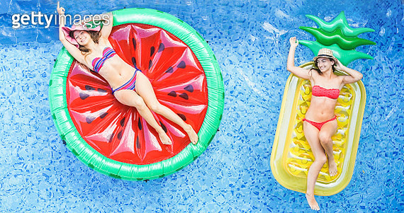 High Angle View Of Female Friends Relaxing On Inflatable Rings In Swimming Pool - gettyimageskorea