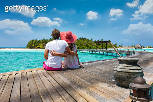Rear View Of Couple Sitting On Pier Against Sky - gettyimageskorea