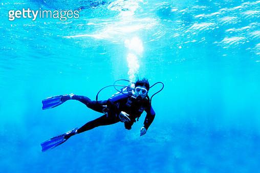 Woman scuba diver in blue ocean. - gettyimageskorea