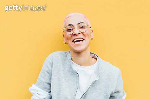 Portrait of happy young woman with short pink hair, wearing glasses - gettyimageskorea