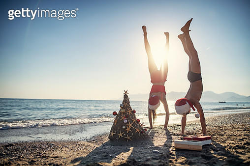 Brother and sister are having fun during summer Christmas. Kids are making handstands near the sand Christmas tree.Nikon D850 - gettyimageskorea