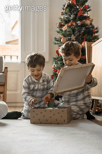 Brothers opening Christmas gifts - gettyimageskorea