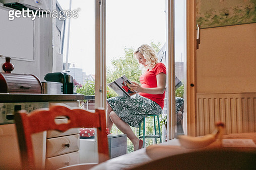 Pregnant woman sitting on balcony looking at photo book - gettyimageskorea