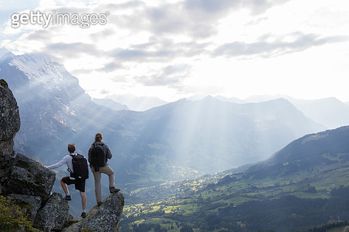 Two hikers look out across valley from rock ridge - gettyimageskorea