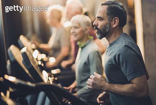 Profile view of athletic mature man jogging on treadmill in a gym. - gettyimageskorea