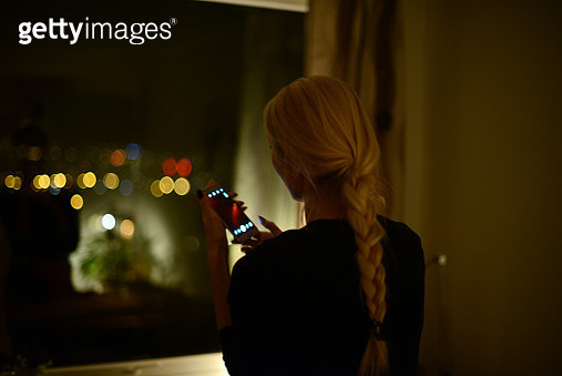 Woman taking photo with her mobile phone through a window at night - gettyimageskorea