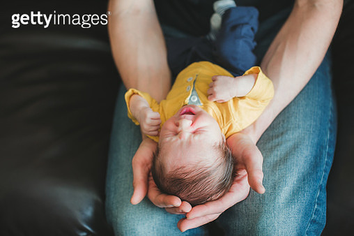 Fathers hands holding yawning newborn - gettyimageskorea