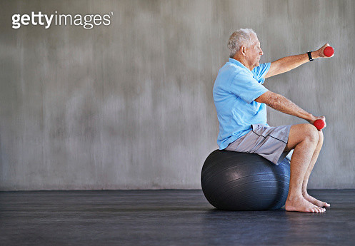 Shot of an elderly man using weights while sitting on a swiss ball - gettyimageskorea