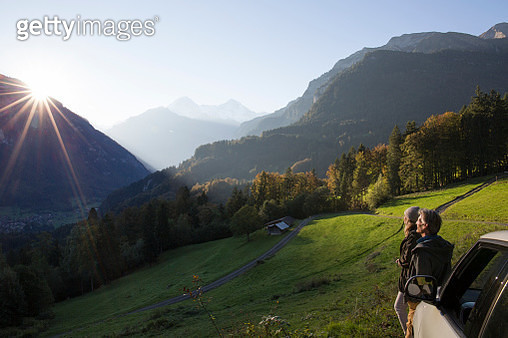 Couple pause by car hood, look out across mtns - gettyimageskorea