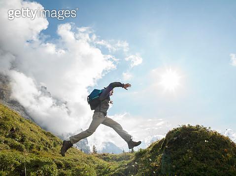 Male hiker bounds along ridge crest, mtns behind - gettyimageskorea