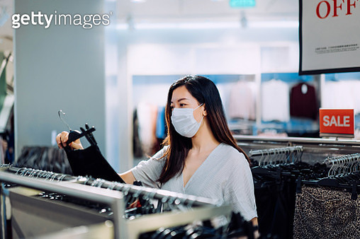 Young Asian woman with protective face mask shopping in a clothing store in the city - gettyimageskorea