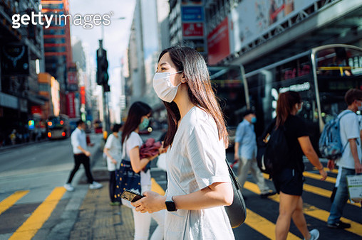 Young Asian woman with protective face mask using smartphone while commuting in downtown city street against crowd of pedestrians and city buildings - gettyimageskorea
