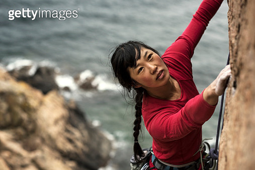 Woman climbing up cliff with ocean in background - gettyimageskorea
