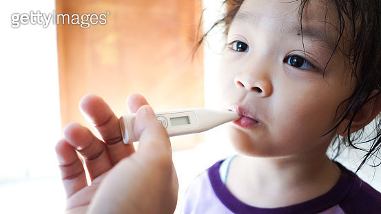 Sick little girl with a thermometer in her mouth - gettyimageskorea