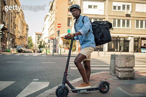 Young African delivery man riding electric scooter and delivering food or packages. - gettyimageskorea