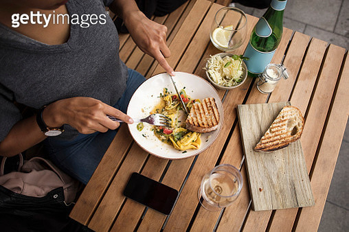 High angle view of woman having lunch at sidewalk cafe table - gettyimageskorea