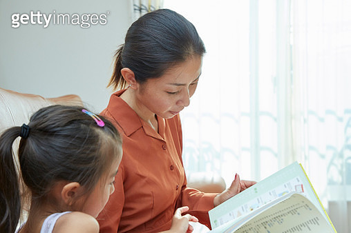 Mother and daughter reading a book in a living room - gettyimageskorea