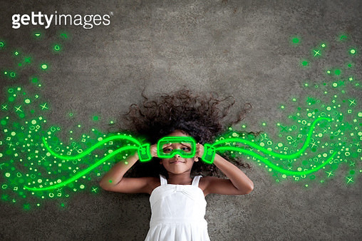 Young black girl wearing white dress and neon-green virtual reality goggles surrounded by imaginative, energetic symbols - gettyimageskorea