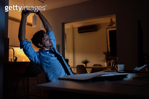 Businessman Stretching At Home Workplace Working Late at Night Feeling Tired - gettyimageskorea