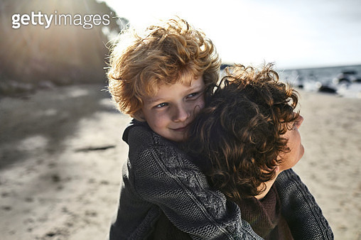 Mother carrying son piggyback on the beach - gettyimageskorea