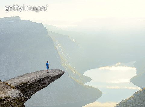 Hiker standing on Trolltunga at Odda, Hordaland county, Norway - gettyimageskorea