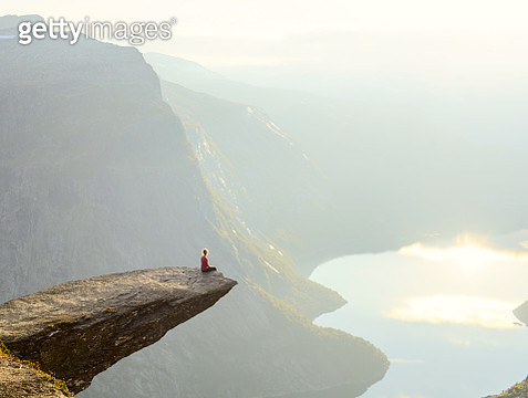 Woman sitting on Trolltunga at Odda, Hordaland county, Norway - gettyimageskorea