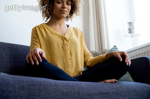 Young woman sitting on couch at home meditating - gettyimageskorea