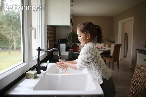 A little girl washing her hands in the kitchen - gettyimageskorea