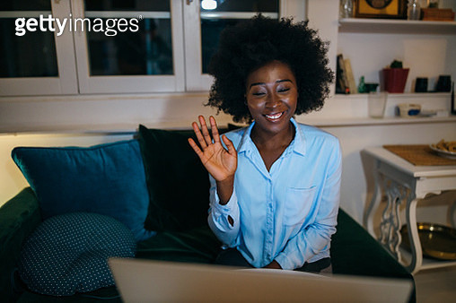 Smiling, young woman sitting at sofa and having a video call. - gettyimageskorea