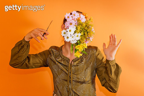 Young woman with flowers covering her face - gettyimageskorea