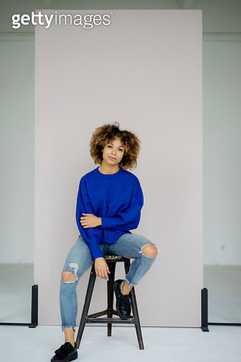 Portrait of serious woman wearing blue pullover sitting on stool - gettyimageskorea