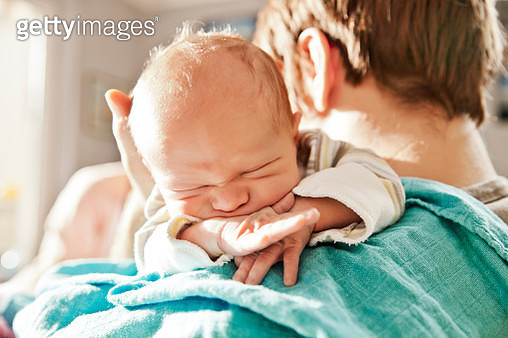 Close-up of father holding his newborn son over the shoulder - gettyimageskorea