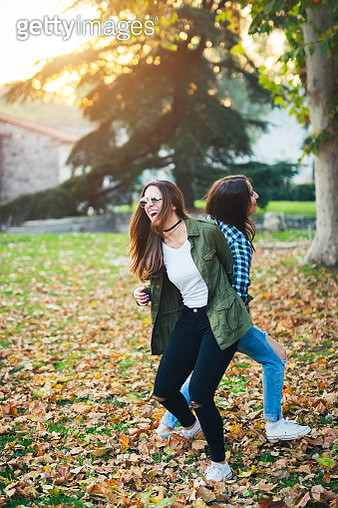 Two cheerful friends fooling around in the park on sunny autumn day - gettyimageskorea