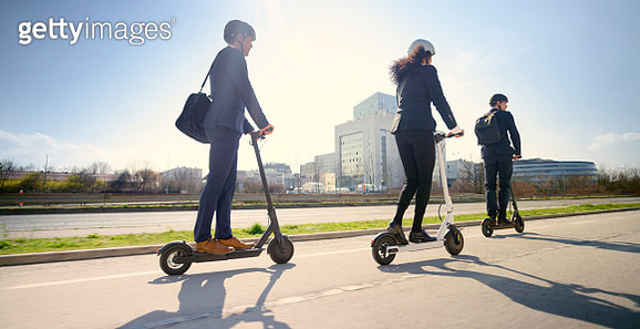 Business people riding electric push scooter in city - gettyimageskorea