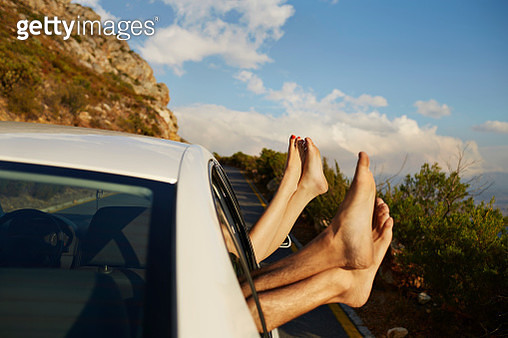 Couple relaxing with feet out of car window - gettyimageskorea